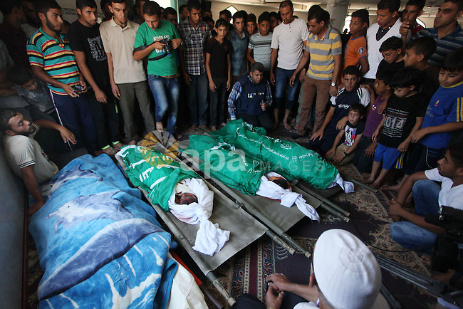 Palestinian relatives mourn over the bodies of members of the Alouh family, killed in an Israeli airstrike during their funeral in Deir al-Balah in the center of the Gaza Strip, on August 20, 2014. An Israeli air strike on a house in the Gaza Strip town of Deir el-Balah killed a pregnant woman, three young children and two male relatives, emergency services said. They named the dead as Rafat Aloah, 32, three of his children, his brother Mohammed 21 and the woman, Nabilah Aloah, whose relationship to the others was not immediately clear. Photo by Ashraf Amra