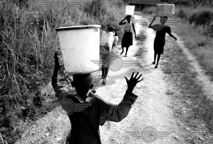 Children carry water home from the river in Shabunda, an isolated village in the tropical rainforest. Democratic Republic of Congo (formerly Zaire).