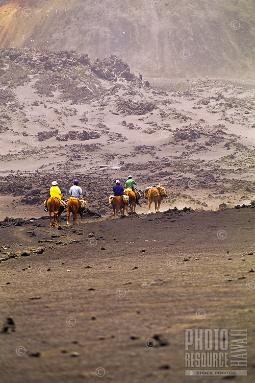 Horseback riders enjoy the unique scenery inside vast Haleakala crater at the Haleakala National Park on Maui.