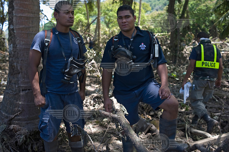 PJ Mai and Ikoea Afoka, volunteer police officers, search through debris for missing persons following the tsunami. More than 170 people died when a tsunami triggered by an 8.3 magnitude earthquake hit Samoa and neighbouring Pacific islands on 29/09/2009. Samoa (formerly known as Western Samoa)..