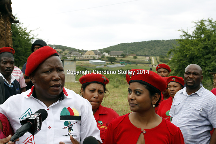 NKANDLA - 11 January 2014 -  EFF leader Julius Malema (left) speaks to the media at a ceremony to hand over a house to a grandmother looking after four children. In the background is the controversial Nkindla residence of President Jacob Zuma. Looking at Malema is Magdalene Moonsamy, the EFF's  head of international relations and solidarity . Picture: Giordano Stolley/Sapa/Allied Picture Press/APP