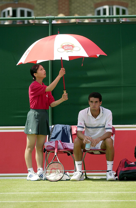 Photo:Ken Brown .11/06/2001. .Stella Artois Championship 2001 .The sun comes out at Queens club as Andre Sa is shielded from the heat by a ball girl during his match with Paradorn Srichaphan..