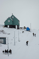 Kapisillit, Greenland - Locals carry their grocery shopping uphill in Kapisillit, Greenland, March 2016. Kapisillit is a settlement in the Sermersooq municipality in southwestern Greenland. In 2016, the settlement has about 60 inhabitants. Kapisillit means the salmon in the Greenlandic language. The name refers to the belief that the only spawning-ground for salmon in Greenland is a river near the settlement.