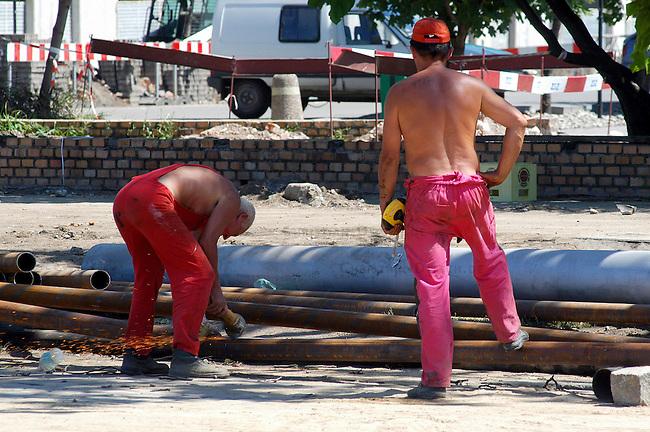 Strassenbau in Wroclaw/Breslau. Da viele Facharbeiter in das westliche Ausland (meistens England) ausgewandert sidn werden viele Arbeistplaetze im Baugewerbe mit Arbeitern aus der Ukraine und Weissrussland besetzt.<br /> Workers repairing a street in Wroclaw.<br /> 17.7.2006, Wroclaw/Poland<br /> Copyright: Christian-Ditsch.de<br /> [Inhaltsveraendernde Manipulation des Fotos nur nach ausdruecklicher Genehmigung des Fotografen. Vereinbarungen ueber Abtretung von Persoenlichkeitsrechten/Model Release der abgebildeten Person/Personen liegen nicht vor. NO MODEL RELEASE! Nur fuer Redaktionelle Zwecke. Don't publish without copyright Christian-Ditsch.de, Veroeffentlichung nur mit Fotografennennung, sowie gegen Honorar, MwSt. und Beleg. Konto: I N G - D i B a, IBAN DE58500105175400192269, BIC INGDDEFFXXX, Kontakt: post@christian-ditsch.de<br /> Bei der Bearbeitung der Dateiinformationen darf die Urheberkennzeichnung in den EXIF- und  IPTC-Daten nicht entfernt werden, diese sind in digitalen Medien nach &sect;95c UrhG rechtlich geschuetzt. Der Urhebervermerk wird gemaess &sect;13 UrhG verlangt.]