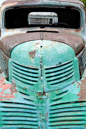 Weathered pickup truck front end in faded green, 1947 Dodge grille.