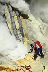 Kawah Ijen Volcano, Java, Indonesia with sulfur mine worker breaking up sulfur deposits at base of condensation pipes.