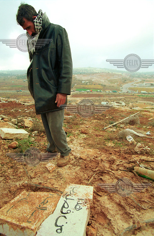 "Atta Jaber stands near a shattered sign that stood above the entrance to his house before it was vandalised by Jewish settlers. The sign reads: ""With God's help, let this house be a house of peace"". .Three days earlier, a Palestinian ambush killed two Jewish settlers driving near Hebron.  The Jewish settlers of Hebron retaliated by taking over the Jaber family house and staying in it until the Israeli army declared it a closed military area. This is the first time Atta Jaber has returned to his house.."
