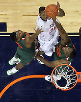 CHARLOTTESVILLE, VA- JANUARY 7: Akil Mitchell #25 of the Virginia Cavaliers is defended by Trey McKinney Jones #4 and Reggie Johnson #42 of the Miami Hurricanes during the game on January 7, 2012 at the John Paul Jones Arena in Charlottesville, Virginia. Virginia defeated Miami 52-51. (Photo by Andrew Shurtleff/Getty Images) *** Local Caption *** Trey McKinney Jones;Reggie Johnson;Akil Mitchell
