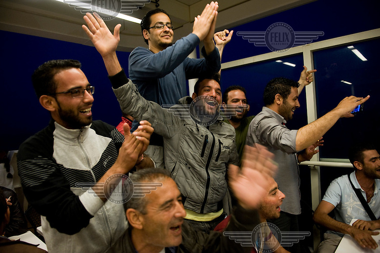 A group of Syrian refugees celebrate their rescue aboard a ferry to mainland Greece after having arrived by inflatable boat on the island of Lesbos having crossed the straits from Turkey. <br />