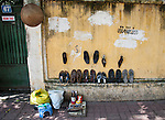 Hanoi, Vietnam, A shoe repair man sets up shop in front of a wall that was hit by demo company graffiti which was covered up, yet to be hit again. photo taken July 2008.