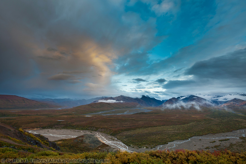 Clouds colored by evening sunshine hover over the river drainages near the Polychrome mountains in Denali National Park, Interior, Alaska.