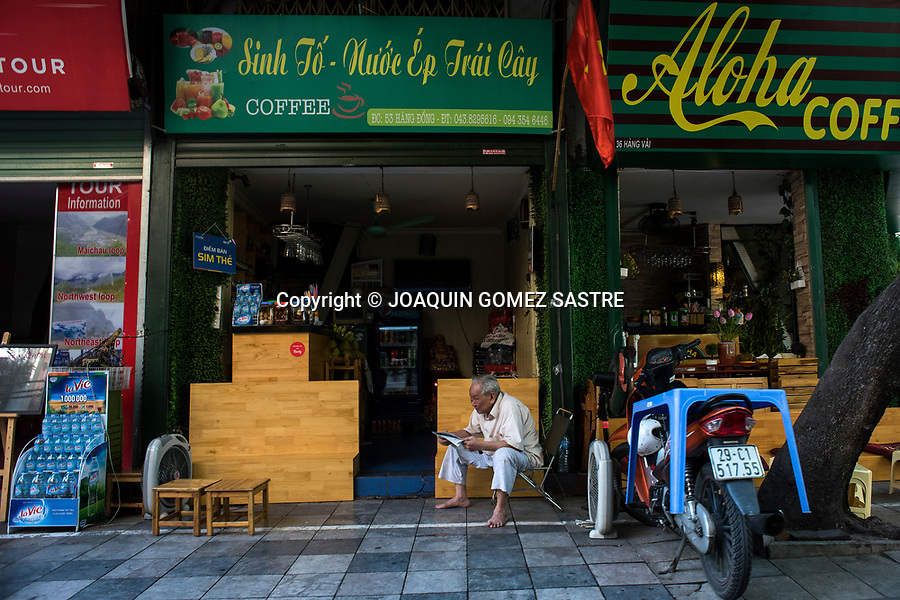 A man reads the newspaper at the entrance of a cafe in the city of Hanoi (Vietnam)<br />