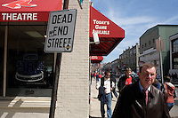 People walk past a business that sells Boston Red Sox tickets on the day of the 2011 season opener at Fenway Park in Boston, Massachusetts, USA.
