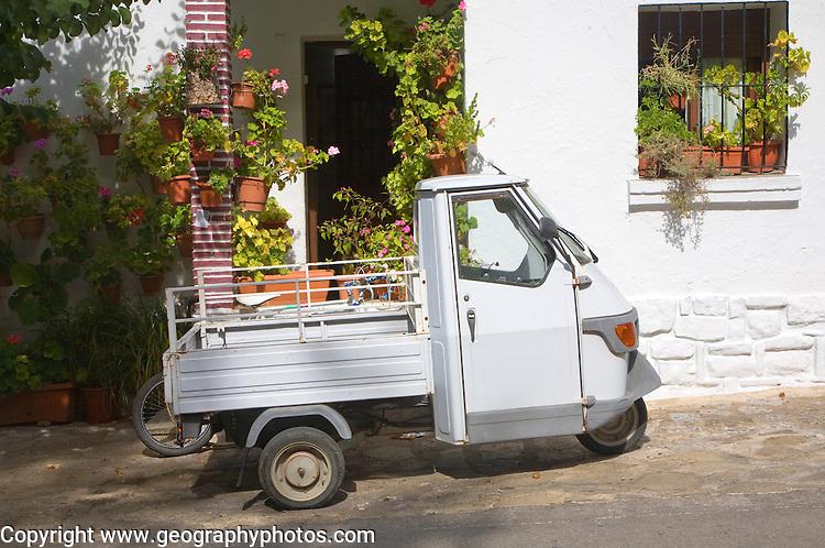 Small three wheeled truck vehicle outside village house Grazalema, Spain