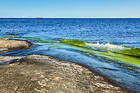 Våg mot klippa och häll vid havet  med horisont på Svartskär i Stockholms skärgård och hav