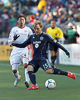Sporting Kansas City defender Seth Sinovic (15) crosses the ball.   In a Major League Soccer (MLS) match, Sporting Kansas City (blue) tied the New England Revolution (white), 0-0, at Gillette Stadium on March 23, 2013.
