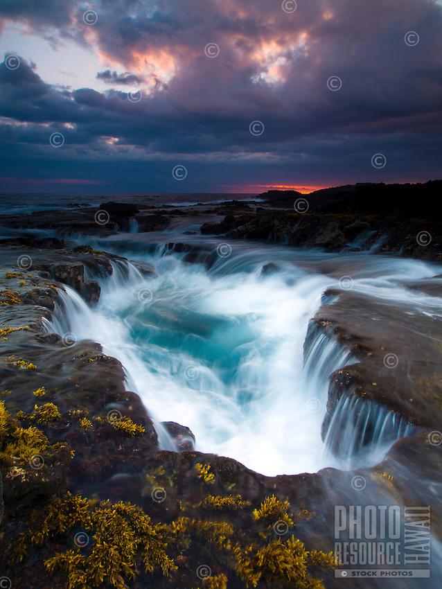 Waves surge in and out of a large puka (or hole) along the Keahole Point coastline during sunset, Kailua-Kona, Big Island.