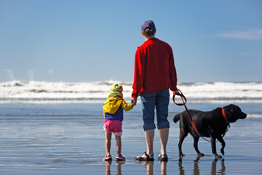 Mother, daughter and dog at Kalalock Beach, Washington Coast, USA