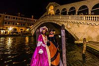 Women in carnival costume (with Rialto Bridge behind), Venice Carnival (Carnevale di Venezia), Venice, Italy.