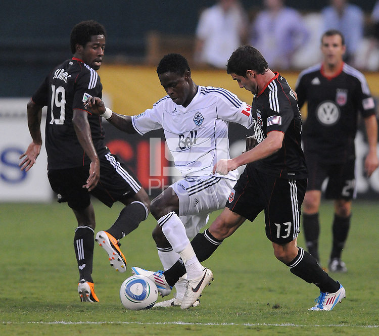 Vancouver Whitecaps FC midfielder Gershon Kofiie (28) shields the ball against D.C. United midfielder Chris Pontius (13) right and midfielder Clyde Simms (19) left. D.C. United defeated The Vancouver Whitecaps FC 4-0 at RFK Stadium, Saturday August 13 , 2011.