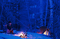 Blue tone winter camping scene with a campfire at night.