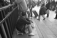 Daytime landscape view of a woman sitting at the B?ij?ng Zhàn in D?ngchéng Q? in Beijing.  © LAN