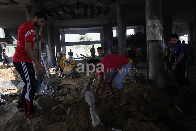 Palestinians inspect the rubble of a destroyed mosque following an Israeli airstrike in Gaza City, on August 9, 2014. Israel launched more than 20 aerial attacks in Gaza early on Saturday and militants fired several rockets at Israel in a second day of violence since a failure to extend an Egyptian-mediated truce that halted a monthlong war earlier this week. The Israeli military said that since midnight it had attacked more than 20 sites in the coastal enclave where Hamas Islamists are dominant, without specifying the targets. Medical officials in Gaza said two Palestinians were killed when their motorcycle was bombed and the bodies of three others were found beneath the rubble of one of three bombed mosques. The air strikes which lasted through the night also bombed three houses, and fighter planes also strafed open areas, medical officials said. Photo by Ashraf Amra