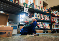 NWA Democrat-Gazette/CHARLIE KAIJO Inesh Vasireddy, 8, of Bentonville reacts as he looks at a book he found during a book sale, Thursday, October 4, 2018 at the Bentonville Public Library in Bentonville.<br />