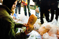 "Tomas, a ""freegan"",  finds a whole squash after rummaging through a garbage bag in front of a supermarket in New York City on April 5, 2006."