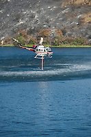 FIre fighting helicopter takes on water from Lauro Reservior during Jesusita Fire, Santa Barbara, California, May 11, 2009