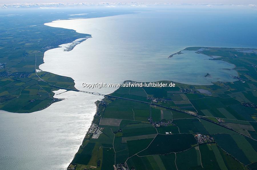 4415/Fehmarnsund :EUROPA, DEUTSCHLAND, SCHLESWIG- HOLSTEIN, 07.06.2005: Der Fehmarnsund ist die Meerenge zwischen der dritgroessten Deutschen Ostseeinsel Fehmarn und dem Festland von Schleswig- Holstein.  Die Fehmarnsundbruecke verbindet die Insel Fehmarn in der Ostsee mit dem Festland bei Großenbrode.<br />Die 963 Meter lange kombinierte Straßen- und Eisenbahnbruecke ueberquert den 1.300 Meter breiten Fehmarnsund, hat eine lichte Hoehe von 23 Metern ueber dem Mittelwasser und wurde 1963 in Betrieb genommen. Zeitgleich wurde die Faehrlinie von Großenbrode-Kai nach Gedser durch die Faehrlinie Puttgarden-Rødby (Daenemark) ersetzt. Durch die Fehmarnsundbruecke und den gleichzeitig gebauten Faehrhafen Puttgarden auf Fehmarn wurde die durchschnittliche Reisezeit auf der so genannten Vogelfluglinie von Hamburg nach Kopenhagen deutlich verkuerzt. Ostsee, Meerenge, Vogelfluglinie, Bundesstrasse B207, Europastrasse E47, Verbindung nach Skandinavien, Insel, Wasser, Meer, Luftaufnahme, Luftbild,  Luftansicht