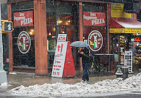 Passer-by outside of Joey Pepperonis Pizza in Chinatown in New York contend with even more snow on Saturday, January 25, 2014. The city has issued a snow alert and meteorologists predict only a dusting to an inch, with gusty winds,  this time around. (© Richard B. Levine)