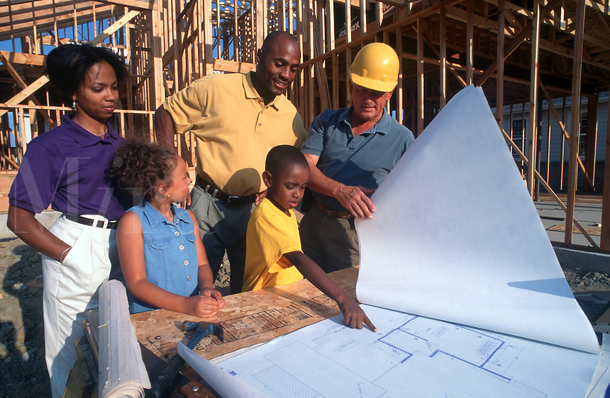 Family looks at plans during house construction.