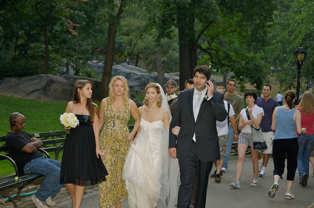 The bride and groom walking in Central park.