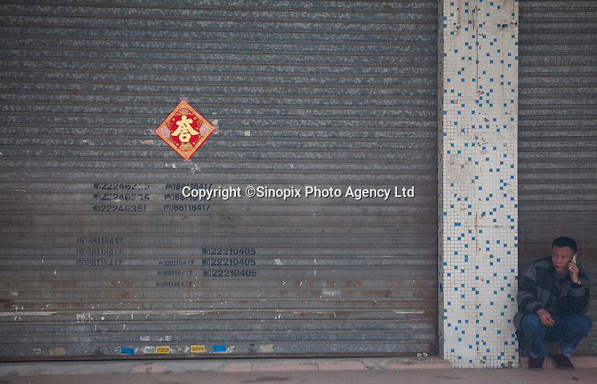 A man speaks on the phone in front of a shuttered shop at the edge of the Yue Yuen Industrial Holdings Limited factory in Dongguan, Guangdong Province, China, 03 March 2015.