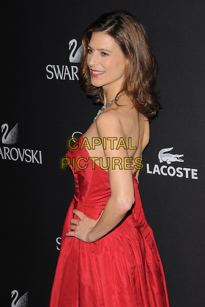 PERREY REEVES.The 11th Annual Costume Designers Guild Awards held at The Beverly Regent Hotel in Beverly Hills, California, USA..February 17th, 2009                                                                     half length red strapless dress hand on hip looking over shoulder .CAP/DVS.©Debbie VanStory/Capital Pictures.