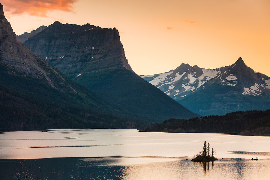 A small boat circles Wild Goose Island in St. Mary Lake at sunset.