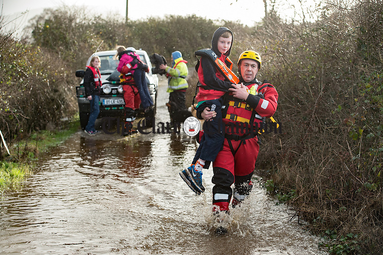 3 carries the Jack Moloney to a waiting boat as his family and some belongings are evacuated from their home. A number of homes at Doorus, O Callaghan's Mills were cut off during the recent heavy rainfall which came with storm Desmond. Photograph by John Kelly.