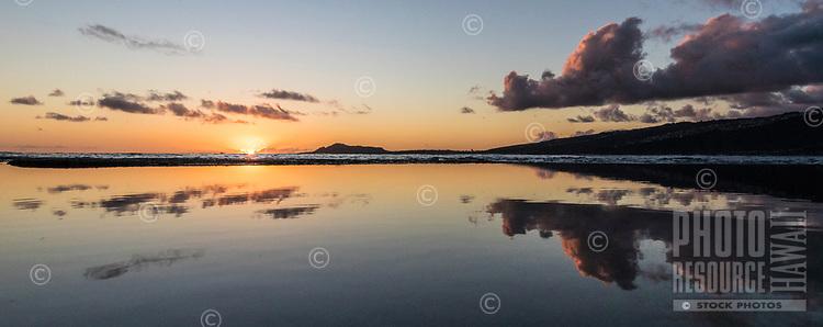 Tidal pools near Koko Head in Hawai'i Kai reflect a fiery sunset over O'ahu; a distant Diamond Head is on the left.