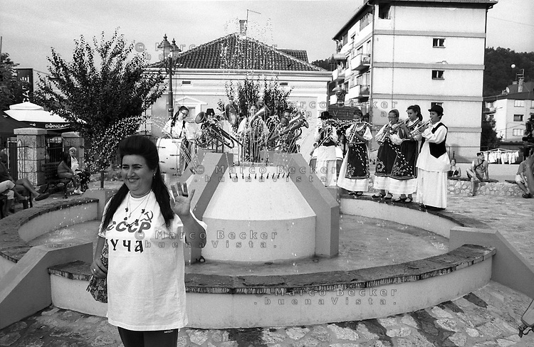 Festival di trombe e ottoni di Guca (Cacak). Una donna con indosso una maglietta con la scritta CCCP posa per una foto davanti a una fontana, sopra la quale suona una banda di donne in abito tradizionale --- Trumpet festival of Guca (Cacak). A woman wearing a CCCP shirt poses for a photo in front of a fountain, over which a band of women wearing traditional clothes is playing