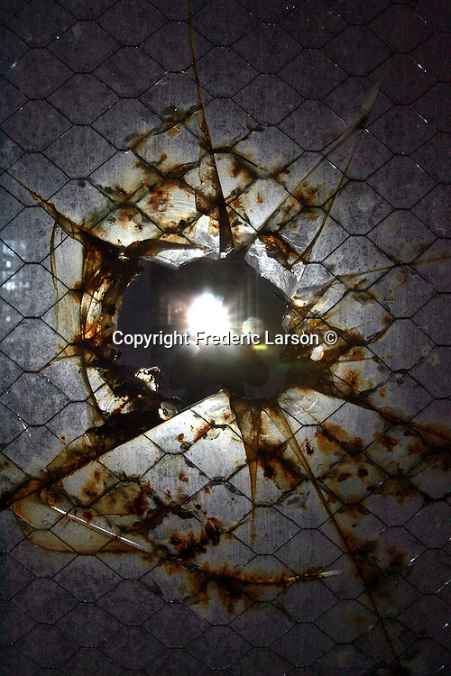 A photographer's flash is reflected through a broken window of the laundry room on Alcatraz. A group of photographers from the Media Alliance overnighted on Alcatraz and documented their tour  in San Francisco California.