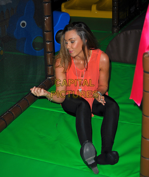 Michelle Heaton opens new children's indoor play area at ZSL Whipsnade Zoo called 'Hullaba-Zoo' along with her nine month old daughter, Faith. Whipsnade Zoo, Bedfordshire, England..October 24th 2012.full length orange top peach pink sitting hands arms profile black tights .CAP/DYL.©Dylan/Capital Pictures.