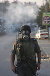 Israeli border policeman wearing gas mask during clashes with Palestinian stone-throwers at the Kalandia checkpoint between the West Bank city of Ramallah and Jerusalem, Thursday, Oct. 8, 2009. President Barack Obama's Mideast envoy finds himself increasingly hamstrung, with Israel's foreign minister on Thursday all but ruling out a peace deal for years to come and the Palestinian leader weakened by his decision not to push for a Gaza war crimes tribunal against Israel.. Photo by Mohamar Awad