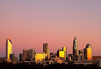 Downtown buildings in the Charlotte NC skyline take on a brilliant glow as they reflect the rising sun. Photo is part of a series of images taken during a 90-minute time period, which captures the sky turning from black to blue then pink/blue. Buildings shown in photo include the Duke Energy headquarters (far left), Wells Fargo buildings (middle), Bank of America tower (tallest on right) and Hearst Tower (tall far right).