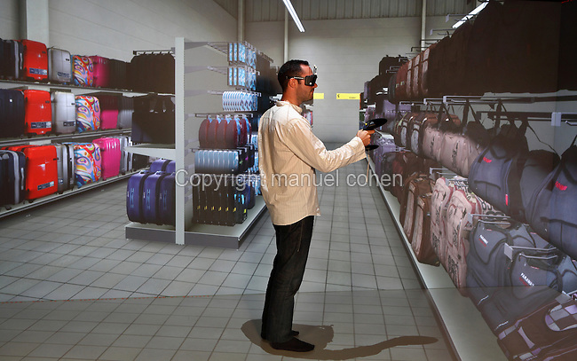 Personnage en situation dans un supermarche, Salle de realite virtuelle avec tableau de bord informatique et trois puissants videoprojecteurs, 3DS, Dassault Systemes, Velizy Villacoublay, Yvelines, France. Man interacting with the projection wall with a luggage shop design in the virtual reality room with computerised rear projection walls and 3 video projectors, 3DS, Dassault Systemes, Velizy Villacoublay, Yvelines, France. Picture by Manuel Cohen