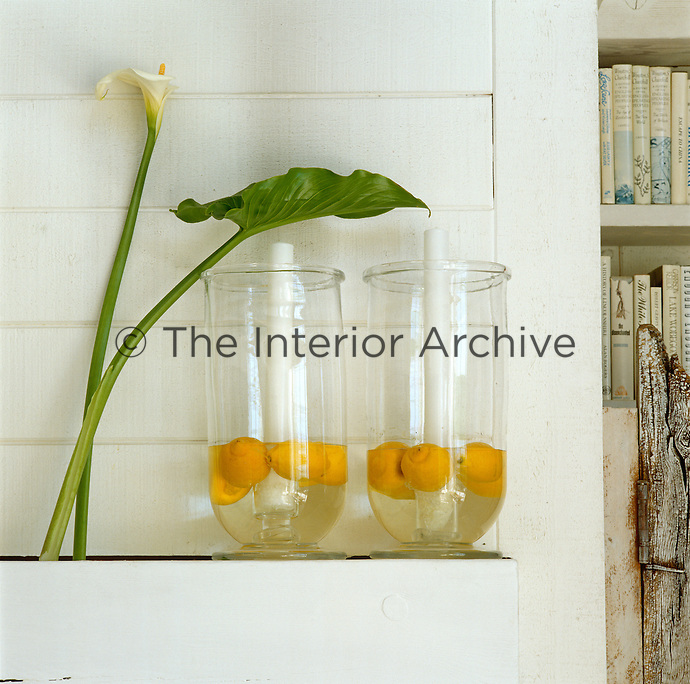 Against the cool white tongue-and-groove of this living room lemons float in a pair of glass lanterns next to an arum lily
