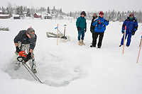 Chase Perrins of Rainy Pass Lodge uses a chain saw to cut a water hole in the ice on Puntilla Lake at the Rainy Pass checkpoint so mushers can get water during the 2010 Iditarod