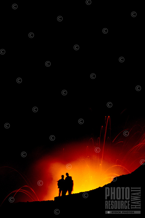 Two people are silhouetted against vivid orange and red fountaining lava during the night at Volcanoes National Park, Hawaii.