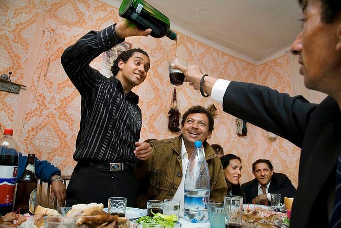 Deronje, Vojvodina, Serbien, 06.05.2007: Auf einer Feier einer Roma-Familie zum Vidovdan, dem Tag ihres Hauspatronen, schenkt der Sohn des Hauses einem Gast teuren Kraeuterlikoer ein.<br />Deronje, Vojvodina, Serbia, 06.05.2007: At a party of a Roma family on Vidovdan, the day of their patron, the son is tossing out herbal liquor to the guests.<br /><br /> [ CREDIT: www.throughmyeyes.de - Merlin Nadj-Torma - phone +49-177-8279119 - merlin@throughmyeyes.de ]