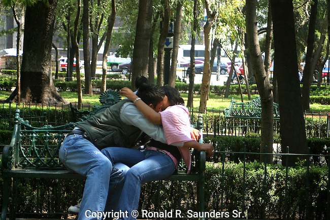 Young couple kiss passionately on park bench (2)